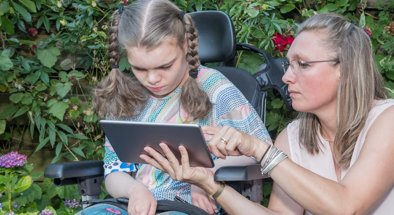 A disabled child learning and communicating with help from a special needs care assistant